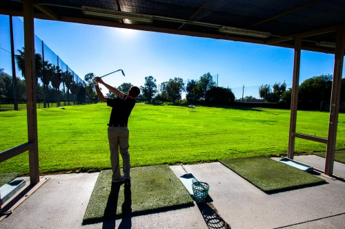 A man uses the River View Golf Course driving range in Orange County